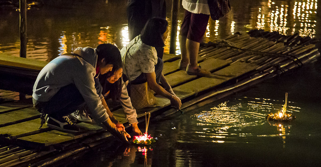 Thai couple float a Krathong at Loy Krathong